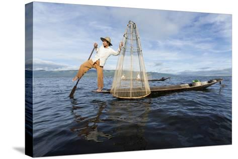 Myanmar, Inle Lake. Young Fisherman Demonstrates a Traditional Rowing Technique-Brenda Tharp-Stretched Canvas Print