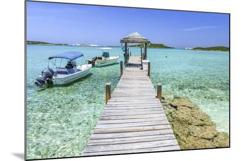 A Wood Pier Leads to Moored Boats and Clear Tropical Waters Near Staniel Cay, Exuma, Bahamas-James White-Mounted Photographic Print