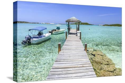 A Wood Pier Leads to Moored Boats and Clear Tropical Waters Near Staniel Cay, Exuma, Bahamas-James White-Stretched Canvas Print