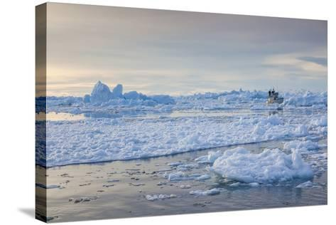 Greenland, Disko Bay, Ilulissat, Fishing Boat in Floating Ice at Sunset-Walter Bibikow-Stretched Canvas Print