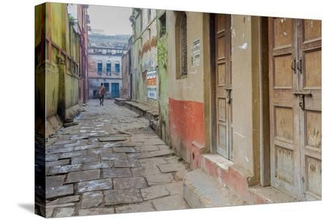 India, Varanasi a Man Walking Down a Stone Tiled Street in the Downtown Area-Ellen Clark-Stretched Canvas Print
