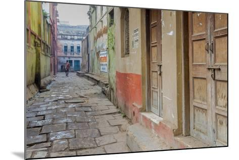 India, Varanasi a Man Walking Down a Stone Tiled Street in the Downtown Area-Ellen Clark-Mounted Photographic Print