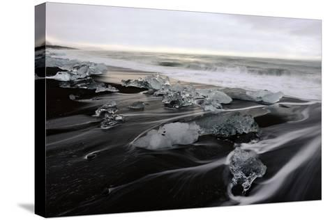 Blocks of Icebergs on Black Sand Beach in Iceland-Raul Touzon-Stretched Canvas Print