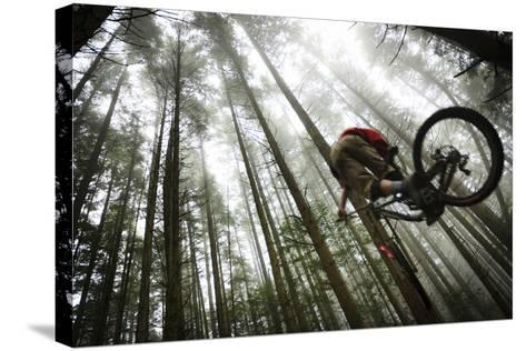 Mountain Biker Catches Air In The Mist Of The Northwest Rainforest Near Bellingham, WA-Jay Goodrich-Stretched Canvas Print