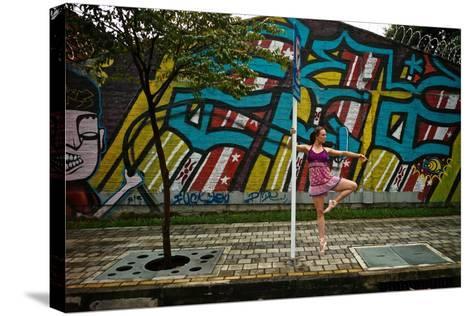 A Dancer Performs A Ballet Pose Outdoors Next To A Urban Grafitti-Kike Calvo-Stretched Canvas Print