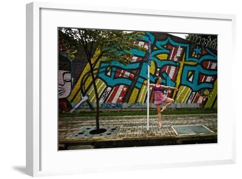 A Dancer Performs A Ballet Pose Outdoors Next To A Urban Grafitti-Kike Calvo-Framed Art Print