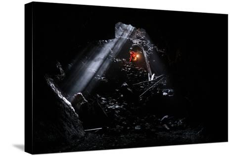 A Man Holding A Propane Lantern Exits The Cheese Cave, A 2,000 Foot Lava Tube-Ben Herndon-Stretched Canvas Print