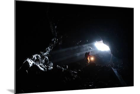 A Man Holding A Propane Lantern Exits The Cheese Cave, A 2,000 Foot Lava Tube-Ben Herndon-Mounted Photographic Print