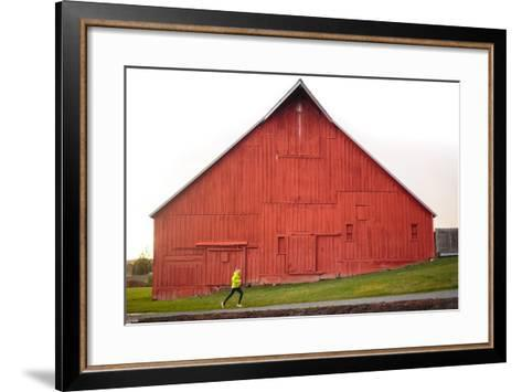 Male Runner Runs Along A Gravel Trail In Front Of Bright Red Barn In UI Arboretum In Moscow, Idaho-Ben Herndon-Framed Art Print