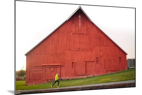 Male Runner Runs Along A Gravel Trail In Front Of Bright Red Barn In UI Arboretum In Moscow, Idaho-Ben Herndon-Mounted Photographic Print