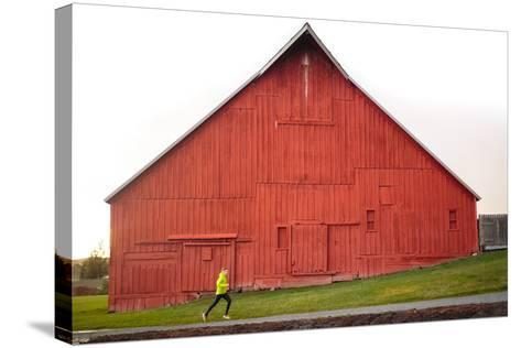 Male Runner Runs Along A Gravel Trail In Front Of Bright Red Barn In UI Arboretum In Moscow, Idaho-Ben Herndon-Stretched Canvas Print