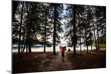 A Man Carrying A Canoe At Priest Lake In North Idaho-Ben Herndon-Mounted Photographic Print