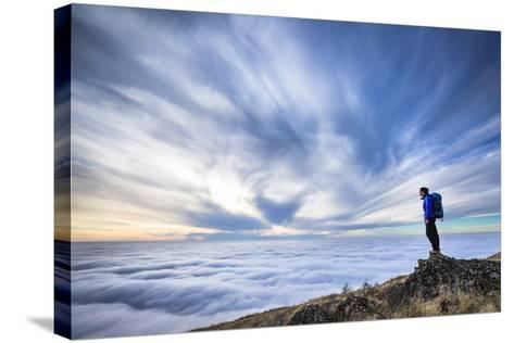 A Female Backpacker Stands On A Rocky Outcrop Above The Clouds At Steptoe Butte, Eastern Washington-Ben Herndon-Stretched Canvas Print