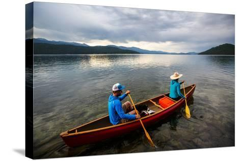 Man & Woman Paddle A Canoe While Shilo The Dog Enjoys The Ride At Sunrise On Priest Lake In N Idaho-Ben Herndon-Stretched Canvas Print