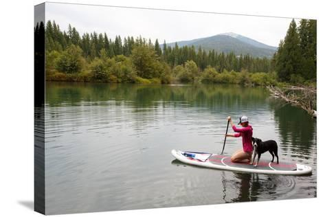 A Woman And Her Dog Shilo On Inflatable SUP Board At The Priest Lake Thoroughfare In North Idaho-Ben Herndon-Stretched Canvas Print