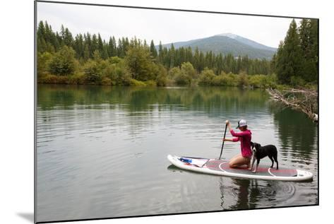A Woman And Her Dog Shilo On Inflatable SUP Board At The Priest Lake Thoroughfare In North Idaho-Ben Herndon-Mounted Photographic Print