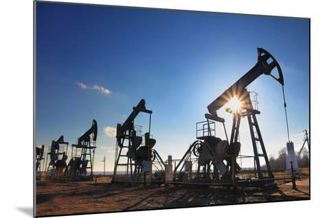 Working Oil Pumps Silhouette against Sun-Kokhanchikov-Mounted Photographic Print