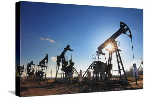 Working Oil Pumps Silhouette against Sun-Kokhanchikov-Stretched Canvas Print