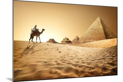 Bedouin on Camel near Pyramids in Desert- Givaga-Mounted Photographic Print