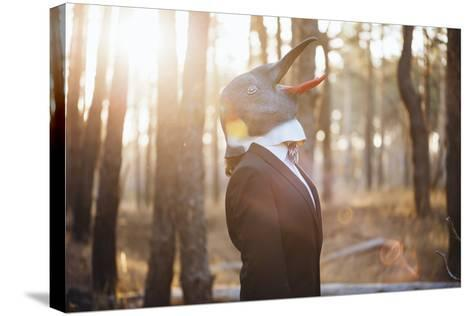 Weird Businessman Wearing a Bird Rubber Mask in the Autumn Sunset Forest- AnastasiaNess-Stretched Canvas Print