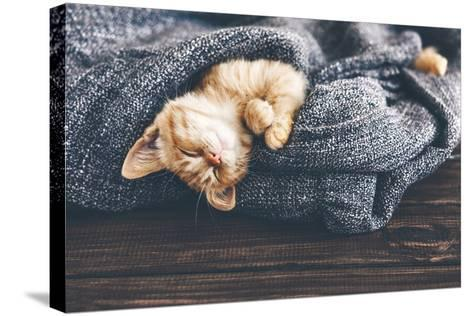 Cute Little Ginger Kitten is Sleeping in Soft Blanket on Wooden Floor-Alena Ozerova-Stretched Canvas Print