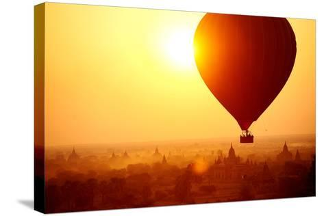 Silhouette of Hot Air Balloon over Bagan in Myanmar, Tourists Watching Sunrise over Ancient City-Daxiao Productions-Stretched Canvas Print