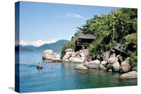 A Paddler Explores the Scenic Rock Formations of the Islands of Lake Malawi, Malawi, Africa, in His- SAPhotog-Stretched Canvas Print