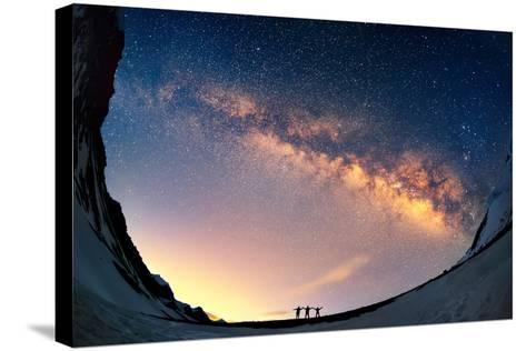 Silhouettes of the People Standing Together Holding Hands against the Milky Way in the Mountains.-Anton Jankovoy-Stretched Canvas Print