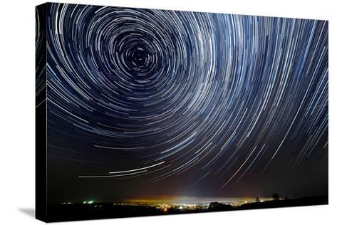 The Motion of Stars around Pole Star in the Night City- AlexussK-Stretched Canvas Print