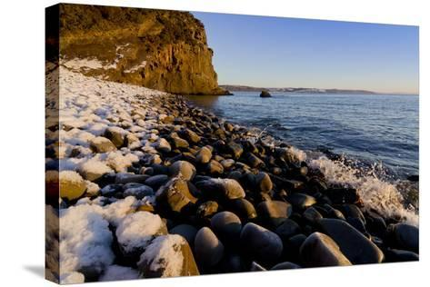 Rocky beach in winter with covering of snow-Charles Bowman-Stretched Canvas Print