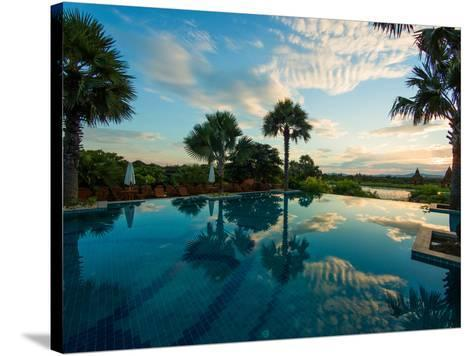 Clouds reflected in the infinity pool at sunrise, Aureum Palace Hotel, Bagan, Mandalay Region, M...--Stretched Canvas Print