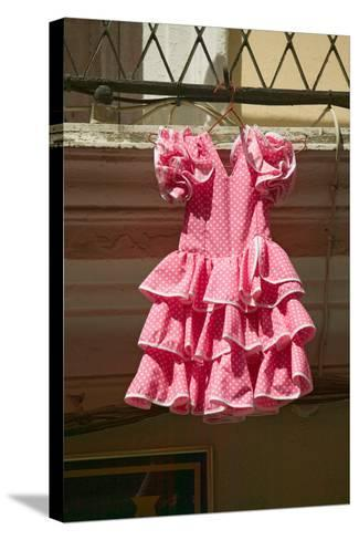 Pink flamenco dress for little girl hangs in Centro old district of Sevilla Spain--Stretched Canvas Print