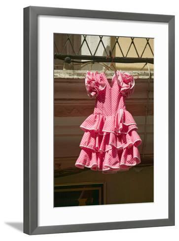 Pink flamenco dress for little girl hangs in Centro old district of Sevilla Spain--Framed Art Print