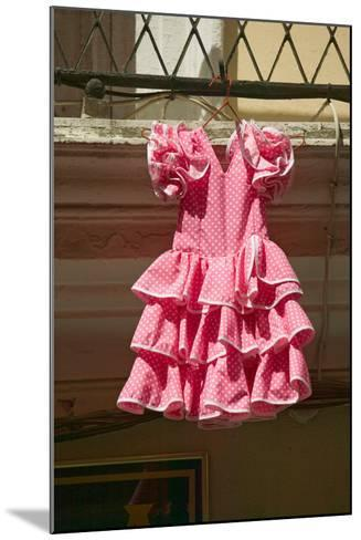 Pink flamenco dress for little girl hangs in Centro old district of Sevilla Spain--Mounted Photographic Print