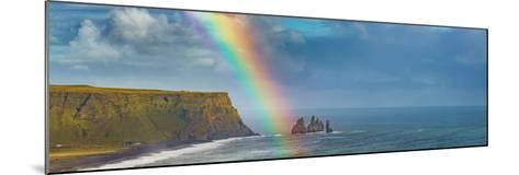 Rainbow over basalt sea stacks, Iceland--Mounted Photographic Print