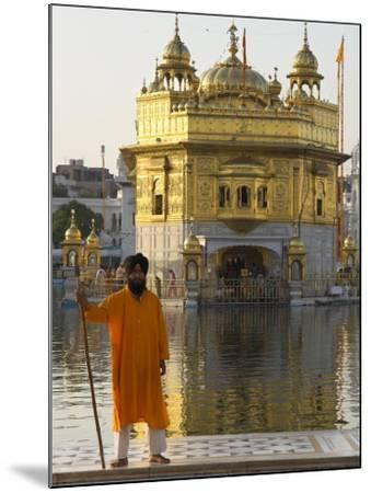 Shrine Guard in Orange Clothes Holding Lance Standing by Pool in Front of the Golden Temple-Eitan Simanor-Mounted Photographic Print