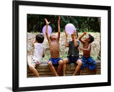 Local Boys Toss Balloons Outside Preah Kahn Temple, Siem Reap, Cambodia-Daniel Boag-Framed Photographic Print