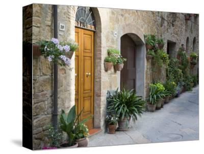Flower Pots and Potted Plants Decorate a Narrow Street in Tuscan Village, Pienza, Italy-Dennis Flaherty-Stretched Canvas Print