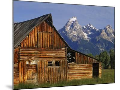 Weathered Wooden Barn Along Mormon Row with the Grand Tetons in Distance, Grand Teton National Park-Dennis Flaherty-Mounted Photographic Print