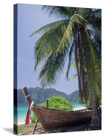 Wooden Boat Beneath Palm Trees on Beach, off the Island of Phuket, Thailand-Ruth Tomlinson-Stretched Canvas Print