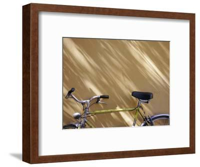 Bicycle Leaning against a Shadowed Yellow Wall, Parma, Italy-Gina Martin-Framed Photographic Print