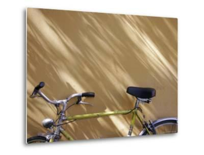 Bicycle Leaning against a Shadowed Yellow Wall, Parma, Italy-Gina Martin-Metal Print