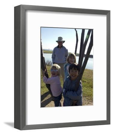 Kids Climb a Tree as their Grandpa Looks On, Washington, D.C.-Stacy Gold-Framed Photographic Print