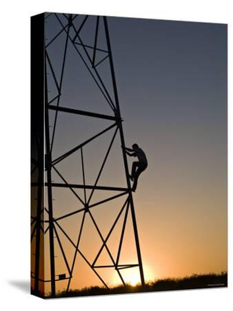 Silhouette of a Man Climbing a High Power Electric Line Tower, California-Dawn Kish-Stretched Canvas Print