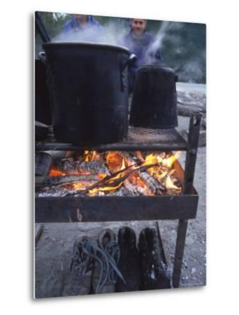 Two Men at Camp Are Drying their Shoes under Camp Cook Fire-Kate Thompson-Metal Print