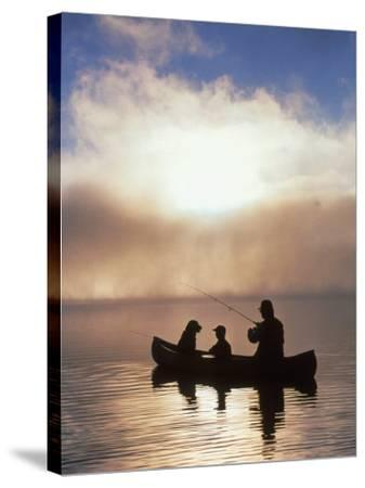 Silhouetted Father and Son Fishing from a Canoe-Bob Winsett-Stretched Canvas Print