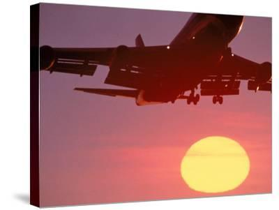 Airplane in Flight During Sunrise, Sunset-Mitch Diamond-Stretched Canvas Print