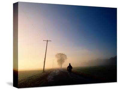 A Lone Jogger Runs Down a Rural Road in Early Morning Fog-Melissa Farlow-Stretched Canvas Print