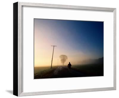 A Lone Jogger Runs Down a Rural Road in Early Morning Fog-Melissa Farlow-Framed Premium Photographic Print
