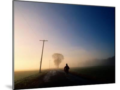 A Lone Jogger Runs Down a Rural Road in Early Morning Fog-Melissa Farlow-Mounted Premium Photographic Print
